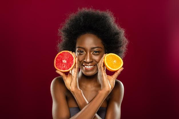 Цитрусовые. радостная счастливая женщина улыбается вам, наслаждаясь едой цитрусовых