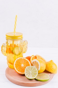 Citrus fruits and juice on wooden board