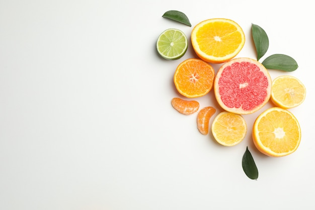 Citrus fruits and leaves on white background, space for text