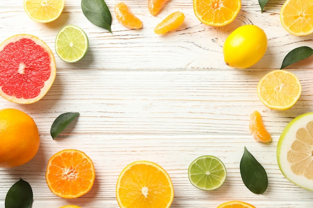 Citrus fruits and leaves on wooden background, space for text