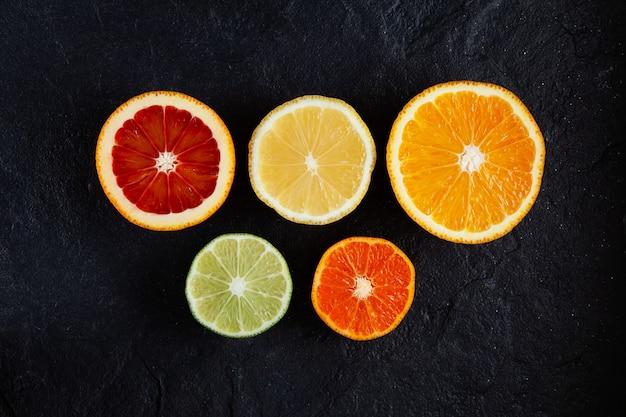 暗い石の背景の上面図に柑橘系の果物レモンタンジェリンライム赤オレンジ