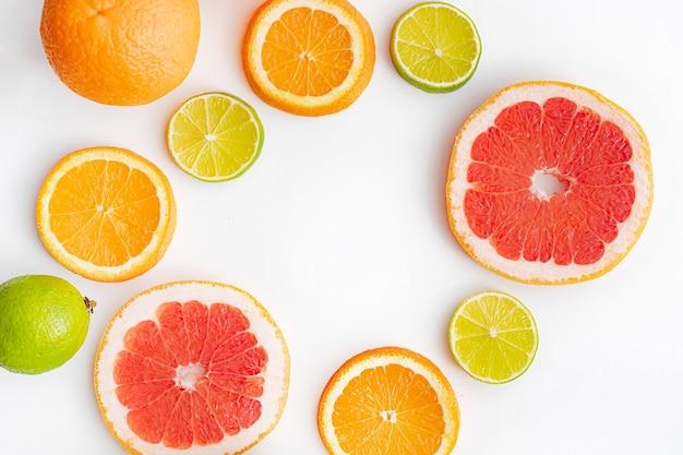 Нарезаются цитрусовые на белой поверхности. цветные плоды. семейство цитрусовых.