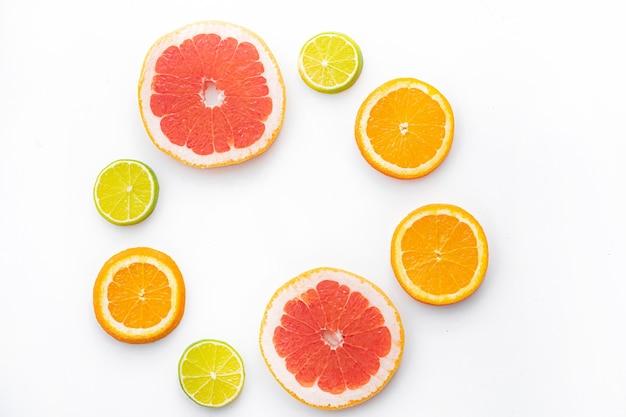 Нарезаны цитрусовые на белой стене. цветные плоды. семейство цитрусовых. Premium Фотографии