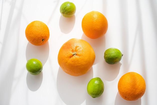 Цитрусовые на белой стене. плоды и тени. копировать пространство
