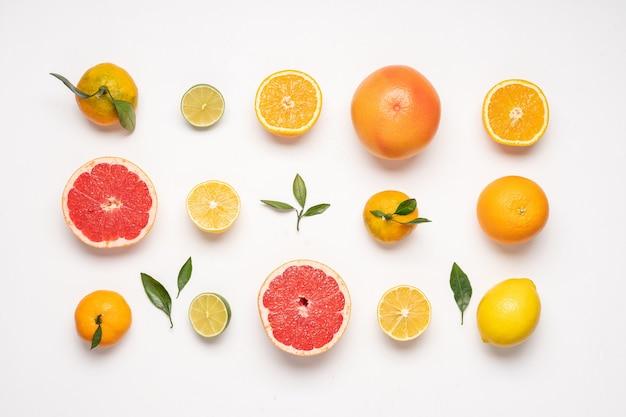白い背景の上の柑橘系の果物明るいレモングレープフルーツライムオレンジみかんの上面図パターン