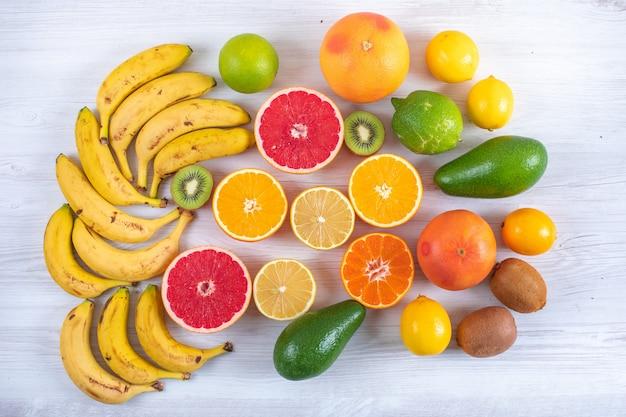 白い木製テーブルオレンジグレープフルーツレモンライムバナナタンジェリントップビューに柑橘系の果物