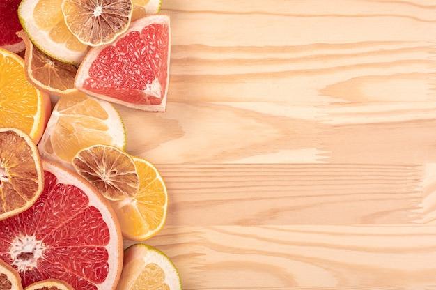 木製の背景に柑橘系の果物。柑橘系の果物のスライスがカットされ、木製のテーブルに配置されます