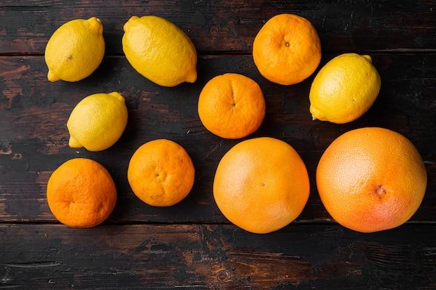 Набор цитрусовых, апельсина, грейпфрута и мандарина, на фоне старого темного деревянного стола, плоский вид сверху