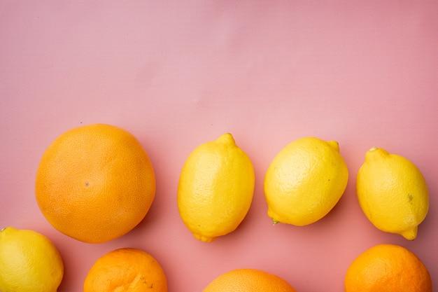 Набор цитрусовых, апельсина, грейпфрута и мандарина, на розовом текстурированном летнем фоне, плоская планировка, вид сверху, с местом для текста