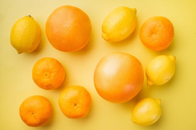 Набор цитрусовых, апельсина, грейпфрута и мандарина, на желтом текстурированном летнем фоне, плоский вид сверху