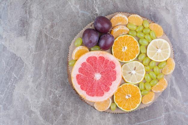 Цитрусовые, сливы и виноград на куске дерева.