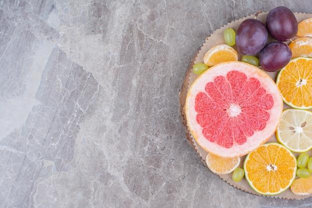 Agrumi, prugne e uva sul pezzo di legno.