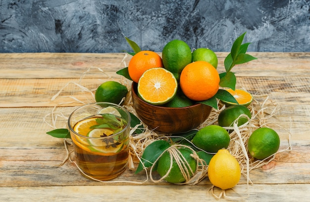 Citrus fruits in pot with herbal tea on wooden board and blue marble surface