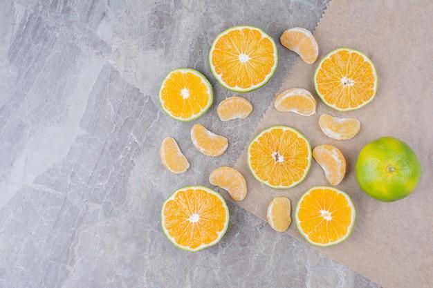 돌 배경에 흩어져있는 감귤류의 과일.