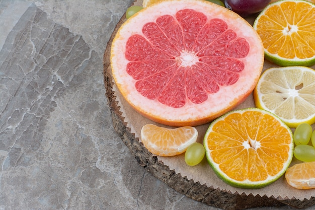 Citrus fruits slices and grapes on wood piece.