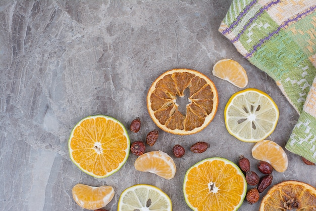 Citrus fruits slices and rosehips on stone background.