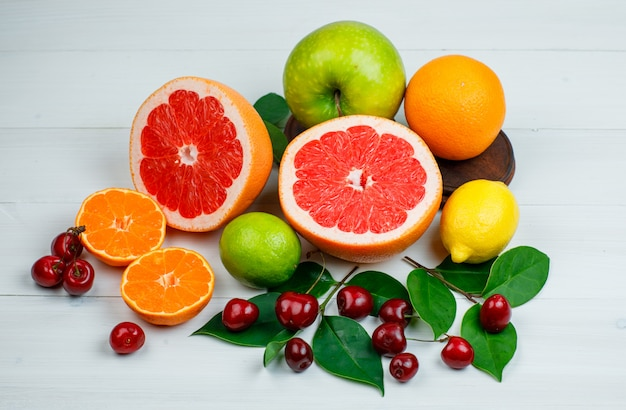 Citrus fruits with apple, cherries, leaves flat lay on a wooden table