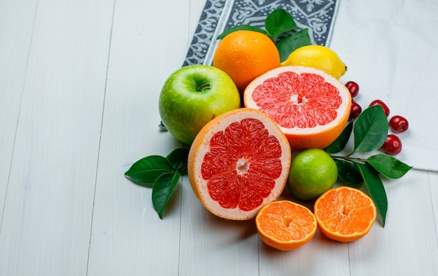 Citrus fruits with apple, cherries, leaves on wooden and picnic cloth table, high angle view.