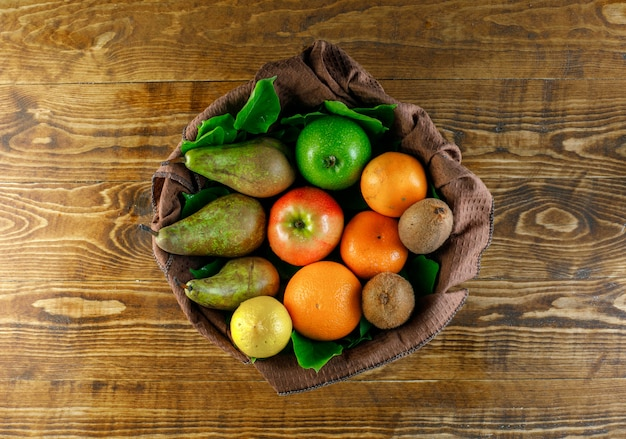 Citrus fruits with apples, pear, kiwi, leaves on wooden table, top view.