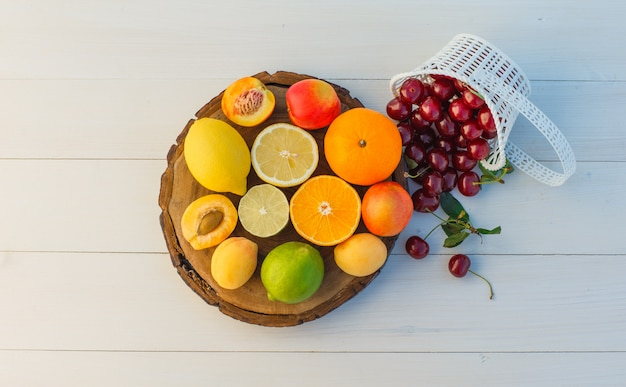 Citrus fruits with cherries, apricots, nectarines flat lay on cutting board and wooden background