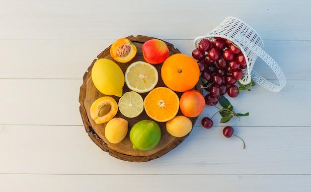 Цитрусовые с вишней, абрикосами, нектаринами, лежат на разделочной доске и деревянном фоне