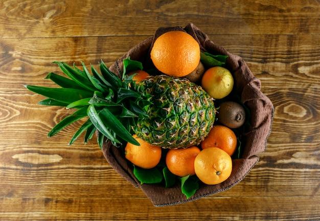 Цитрусовые с киви, ананас, листья на деревянных и кухонное полотенце, вид сверху.