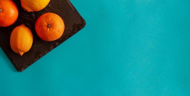 パステルブルーの背景のスレートトレイにオレンジとレモンと柑橘系の果物フラットレイコピースペース