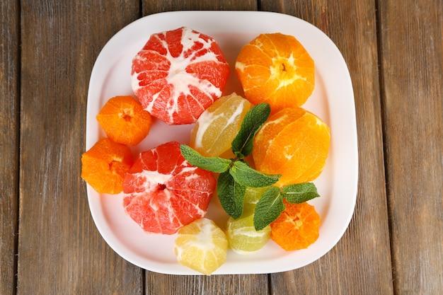 껍질이 없는 감귤류 과일, 접시에, 나무 배경에