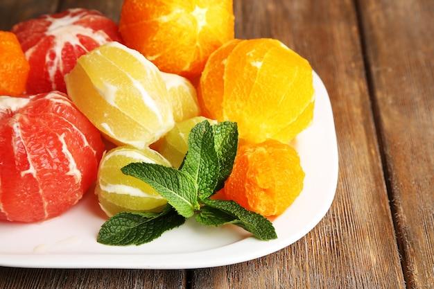 皮のない柑橘系の果物、プレート、木の表面