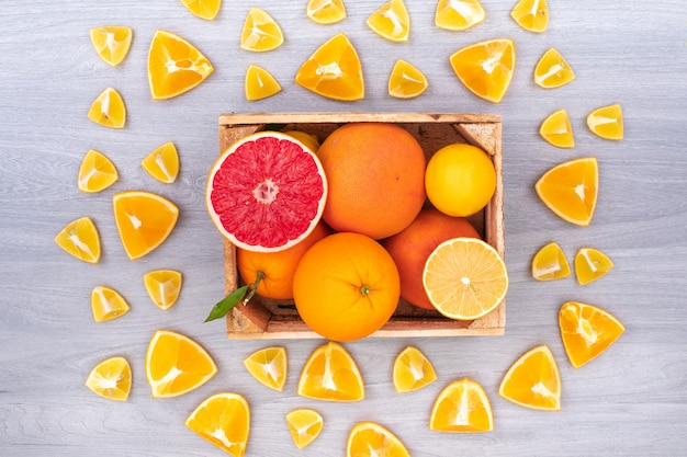 The citrus fruits in the wooden box surrounded with oranges