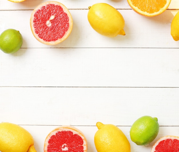 Citrus fruits on wooden table, top view, copyspace background