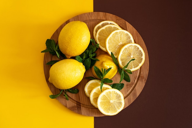 Citrus fruits on a yellow background with copy space.