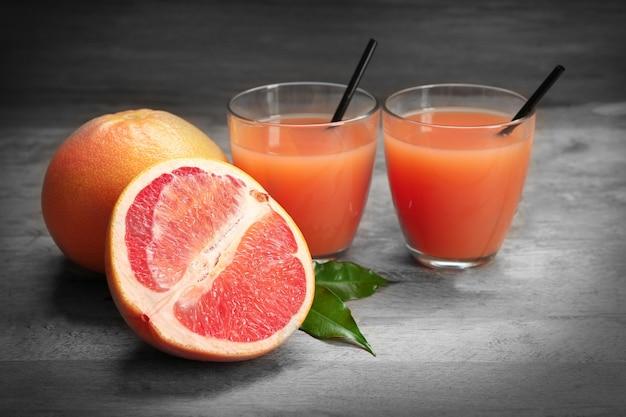 木製のテーブルに柑橘類のジュースと新鮮な果物