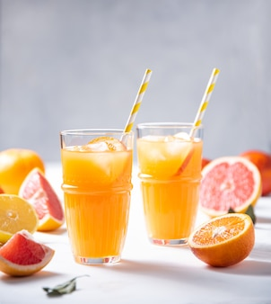 グラス2杯の柑橘系ジュースと灰色の背景に新鮮なフルーツみかん、オレンジ、グレープフルーツ、レモン