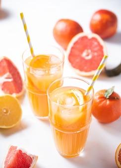 2杯の柑橘類のジュースと白い背景の上の新鮮なフルーツみかん、オレンジ、グレープフルーツ、レモン