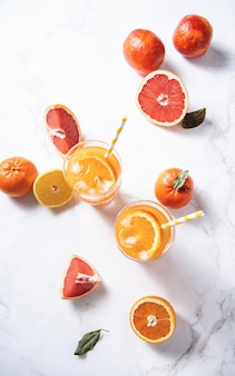 Citrus juice in two glasses and fresh fruit tangerine orange grapefruit and lemon on a  marble background  top view and flat lay