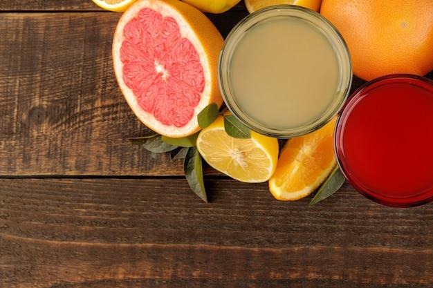 감귤 주스. 갈색 나무 테이블에 신선한 과일과 레몬과 자몽 주스. 을 위한 공간입니다. 위에서 보기