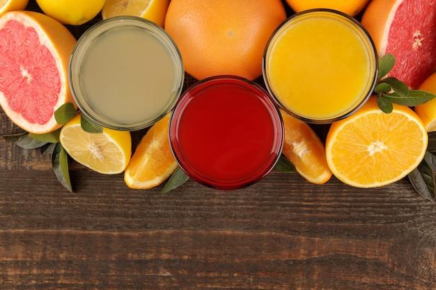 감귤 주스. 갈색 나무 테이블에 신선한 과일과 레몬, 자몽, 오렌지 주스. 을 위한 공간입니다. 위에서 보기