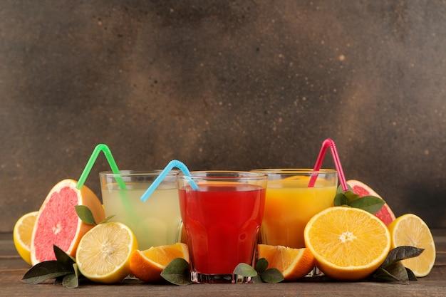 柑橘系のジュース。茶色の木製テーブルに新鮮なフルーツとレモン、グレープフルーツ、オレンジジュース。