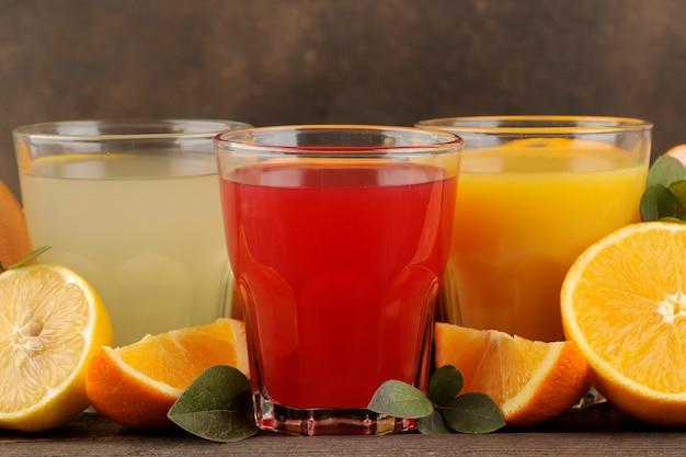 감귤 주스. 갈색 나무 테이블에 신선한 과일과 레몬, 자몽, 오렌지 주스