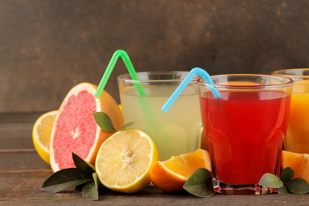 柑橘系のジュース。茶色の木製テーブルに新鮮な果物とレモン、グレープフルーツ、オレンジジュース