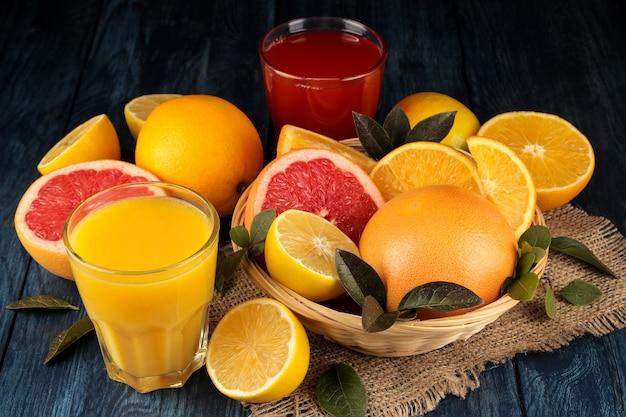 감귤 주스. 푸른 나무 테이블에 신선한 과일과 함께 오렌지와 자몽 주스.