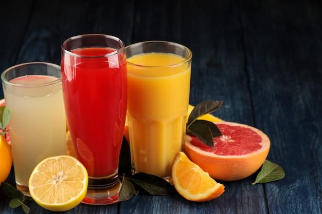 감귤 주스. 푸른 나무 테이블에 신선한 과일과 함께 오렌지, 자몽, 레몬 주스. 텍스트를 위한 공간