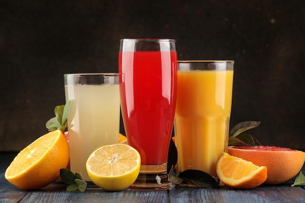 감귤 주스. 푸른 나무 테이블에 신선한 과일과 함께 오렌지, 자몽, 레몬 주스.