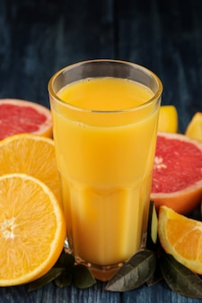 柑橘系のジュース。青い木製のテーブルの上の新鮮な果物とガラスのクローズアップのオレンジジュース。