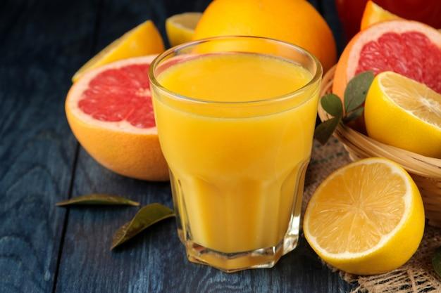 柑橘系のジュース。青い木製のテーブルに新鮮な果物とオレンジジュース。閉じる