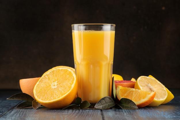 柑橘系のジュース。青い木製のテーブルに新鮮な果物とオレンジジュース。テキスト用のスペースがあります。
