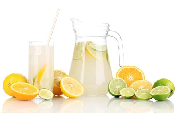 Цитрусовый лимонад в кувшине и стакан цитрусовых вокруг, изолированные на белом