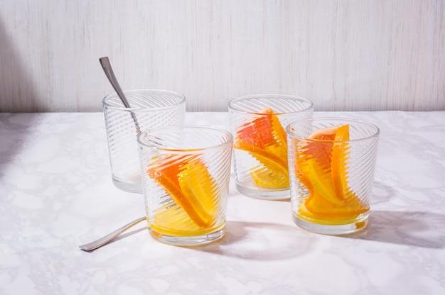 白いテーブルの上のガラスに柑橘類のレモネードの成分。新鮮なミックスフルーツドリンク。健康的な食事、ダイエット