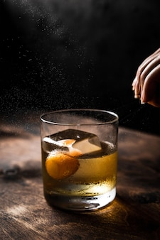 Citrus oil expression shot, a rocks glass with old fashioned cocktail, back light